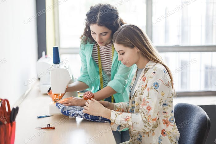 Pretty seamstress teaching girl working with sewing machine at s