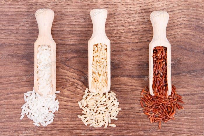 Roter, brauner und weißer Reis mit Holzlöffel auf rustikalem Brett, gesundes Essen