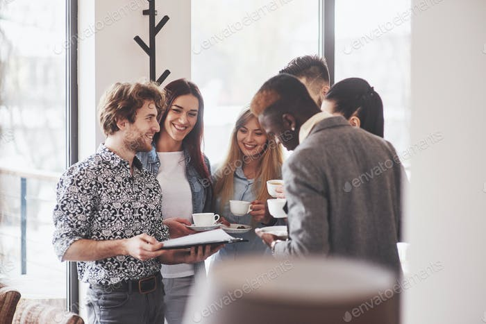 Successful business people are using gadgets, talking and smiling during the coffee break in office