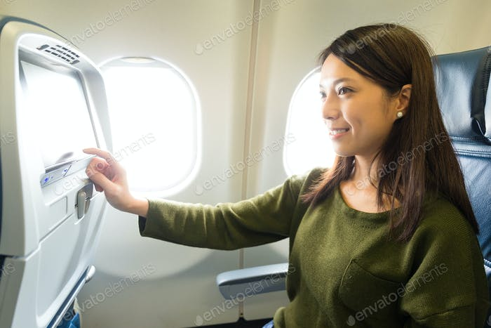 Woman use of the entertainment on airplane