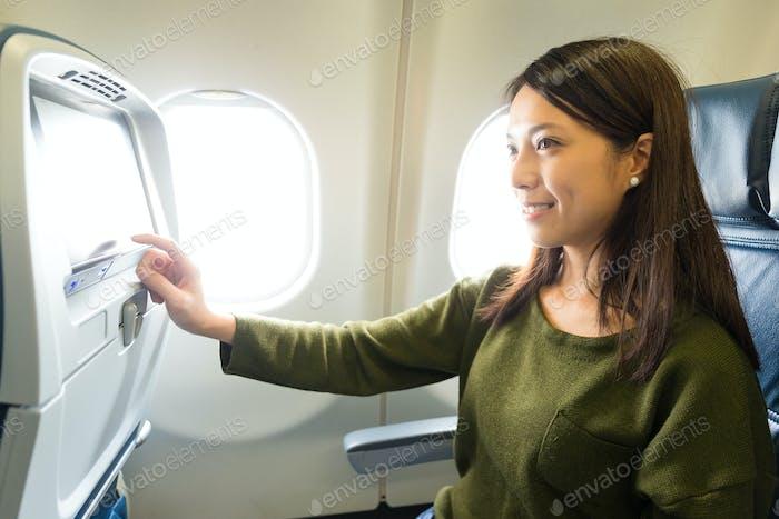Женщина использует развлечения на самолете