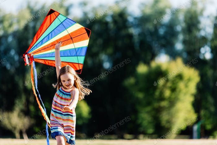 Smiling little girl playing with a colorful kite in the park.