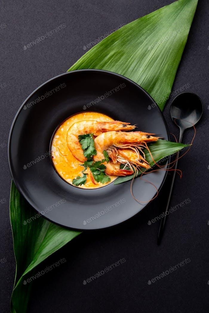 Meeresfrüchte-Suppe dekoriert mit ganzen Garnelen und tropischen Blättern auf schwarzem Teller, schwarzer Hintergrund
