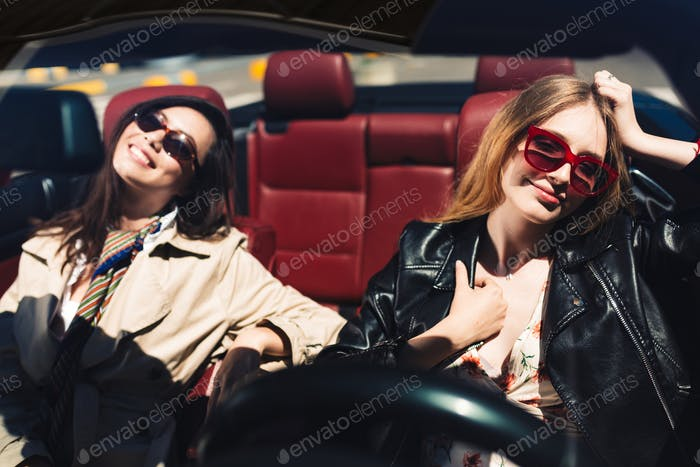 Beautiful smiling girls in sunglasses happily spending time toge