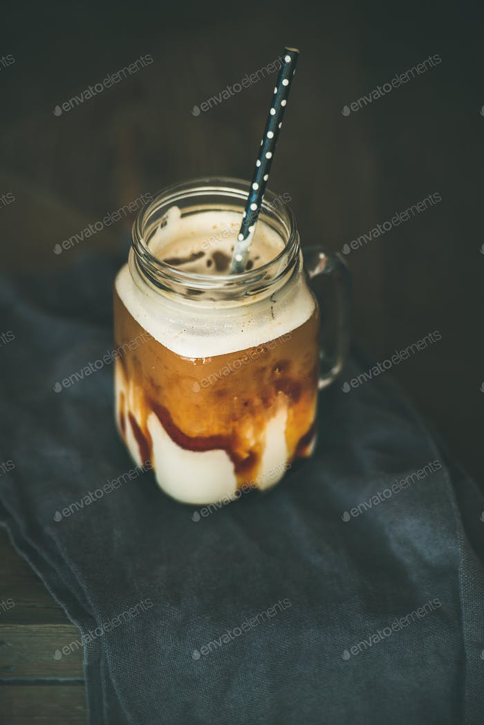 Iced caramel macciato coffee with milk in glass jar, wooden table background