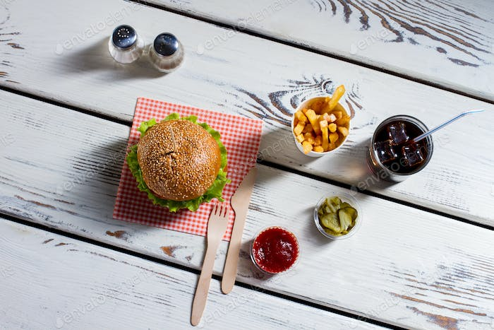 Burger, cutlery and pickle slices.