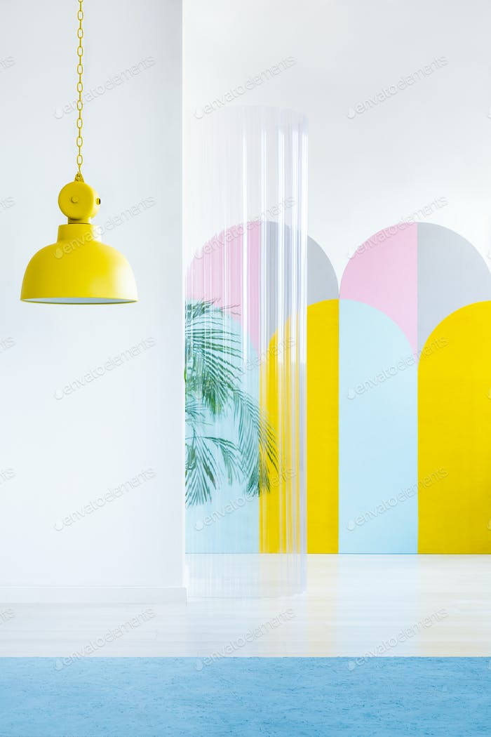 Gelbe Lampe, bunte Tapeten und Kunststoffrohr in einem Raum inter
