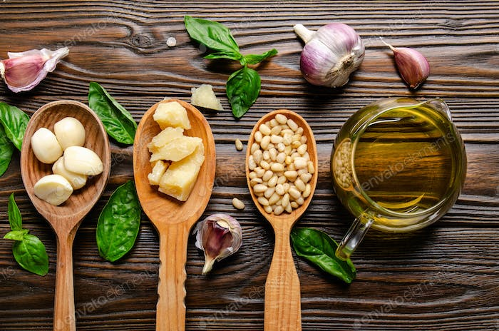 Flat lay view at wooden spoons with food ingredients for pesto genovese sauce on kitchen table