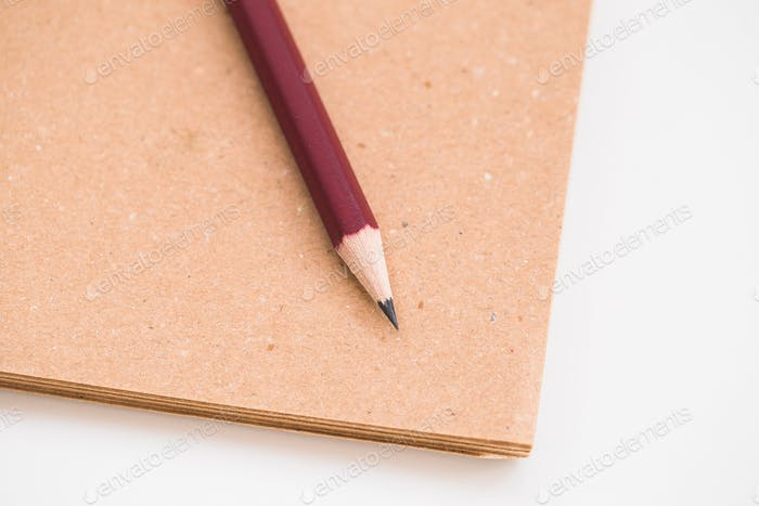 A pencil and notebook isolated on a white background