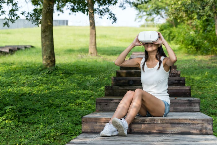 Woman look though VR device at park