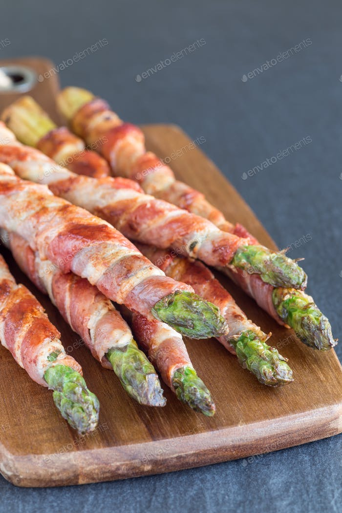 Geen asparagus wrapped with bacon on wooden board, vertical, cop