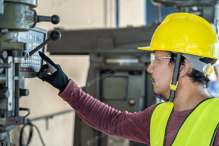 Asian factory engineer in safety suit operating and pressing the professional machinist