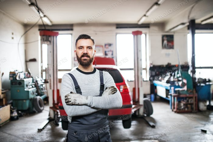 Portrait of a man mechanic in a garage.