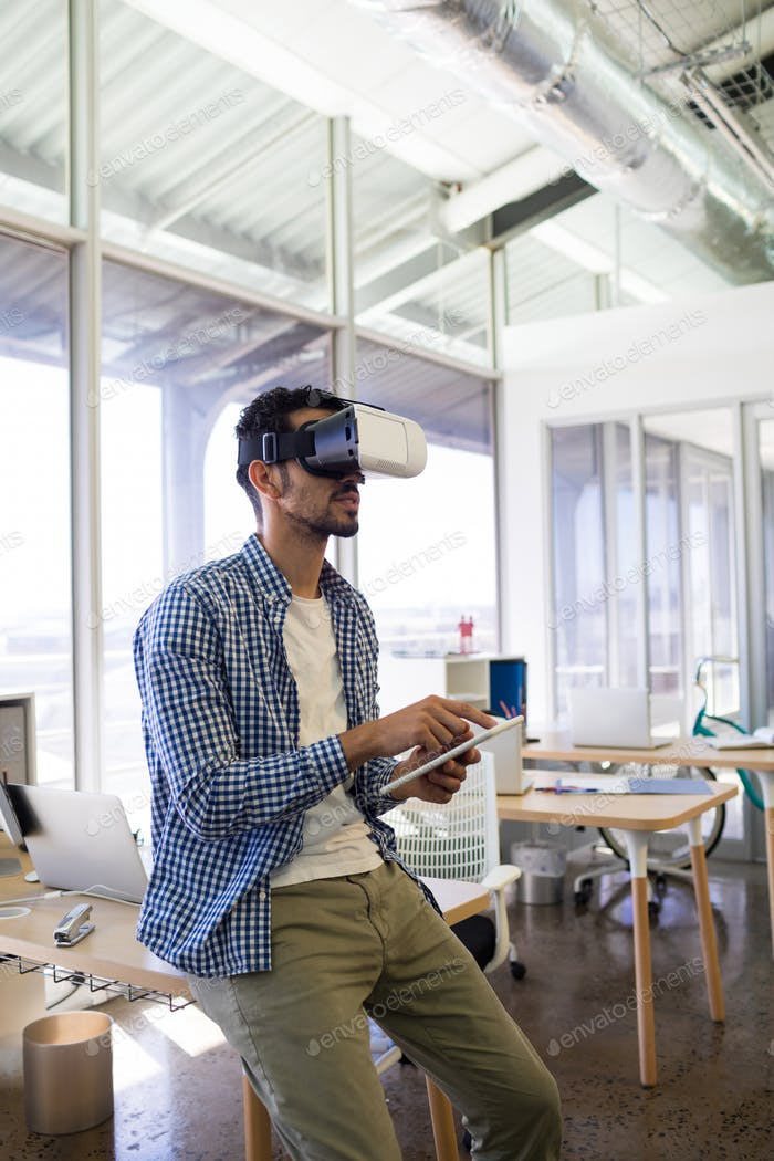 Male executive using virtual reality headset and digital tablet