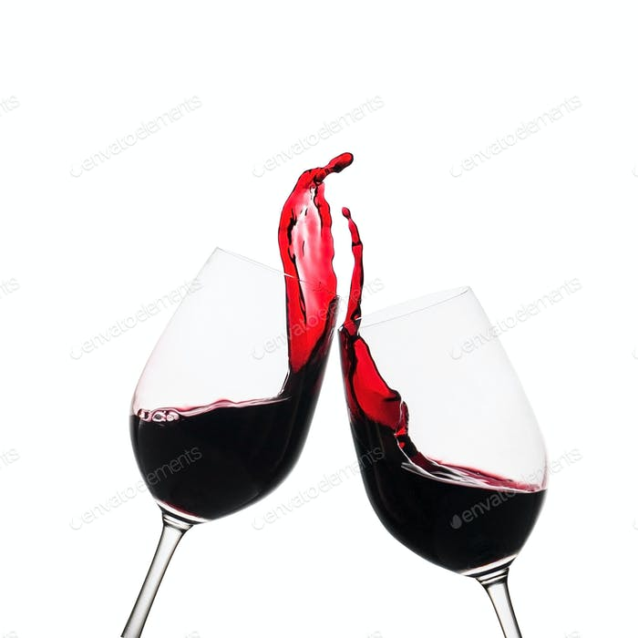Two clinking glasses of red wine in a toast