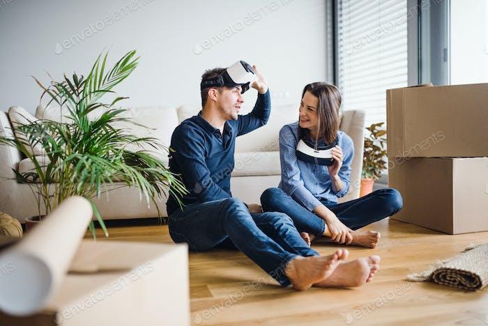 Ein junges Paar mit VR-Brille sitzt auf einem Boden und zieht in einem neuen Zuhause.
