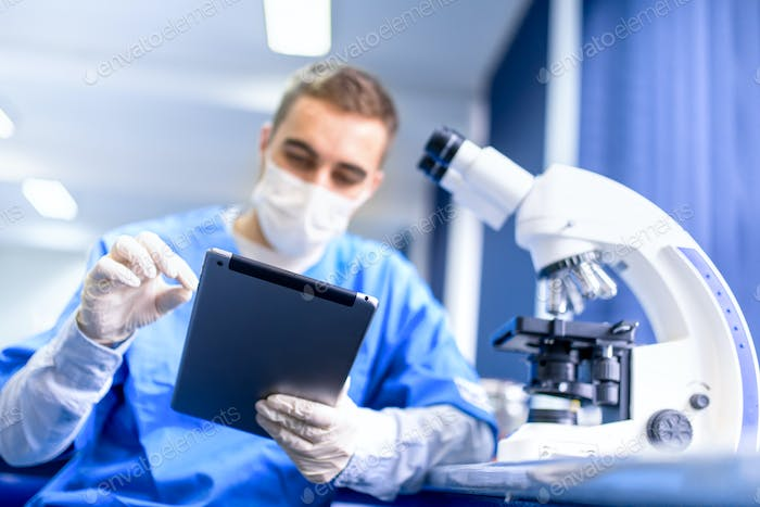 pharmacist working on prescription drugs with modern tablet and microscope