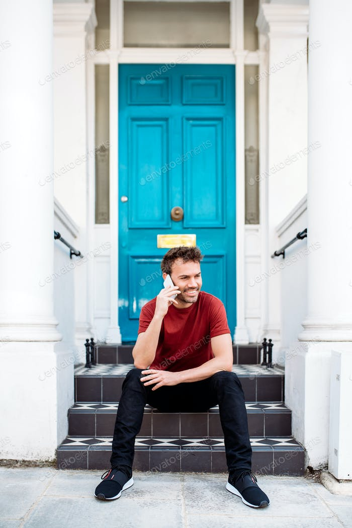 Man sitting in a blue door with mobile phone