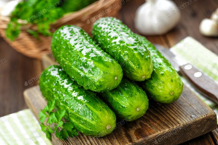 Fresh cucumbers on wooden background close up