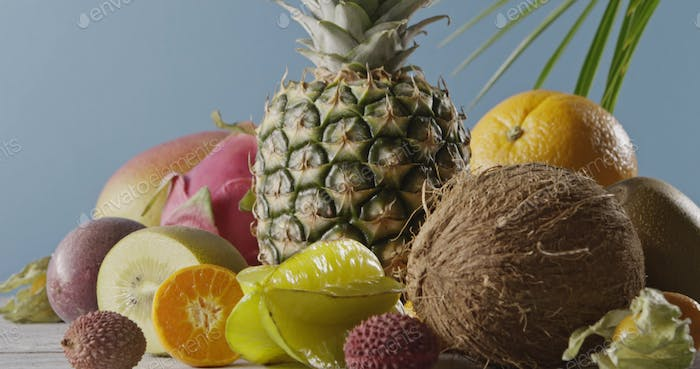 Vertical panoramic upward slow motion with composition from fresh natural exotic fruits on a wooden