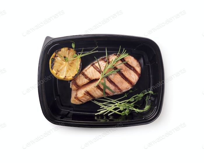 Freshly coocked fish on grill with lemon in black box