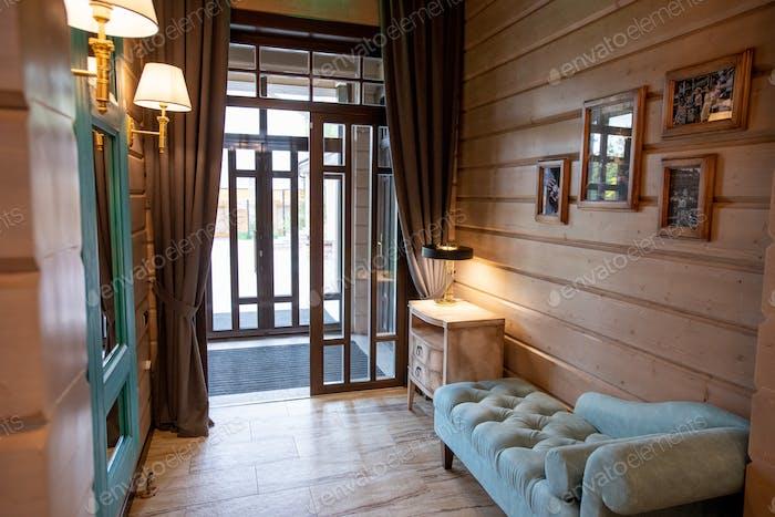 Интерьер небольшой комнаты с мягким бархатным диваном и тумбочкой с лампой на стене