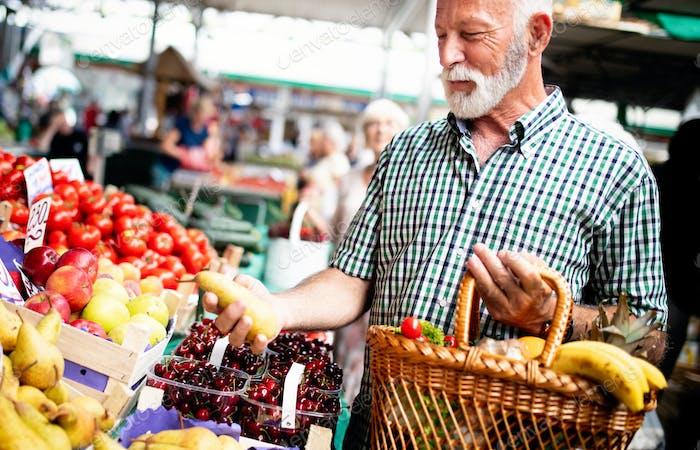 Положительный пожилой мужчина покупает сезонные овощи на местном рынке