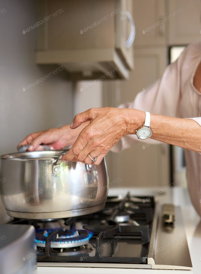 older woman boiling water in pot on stove top