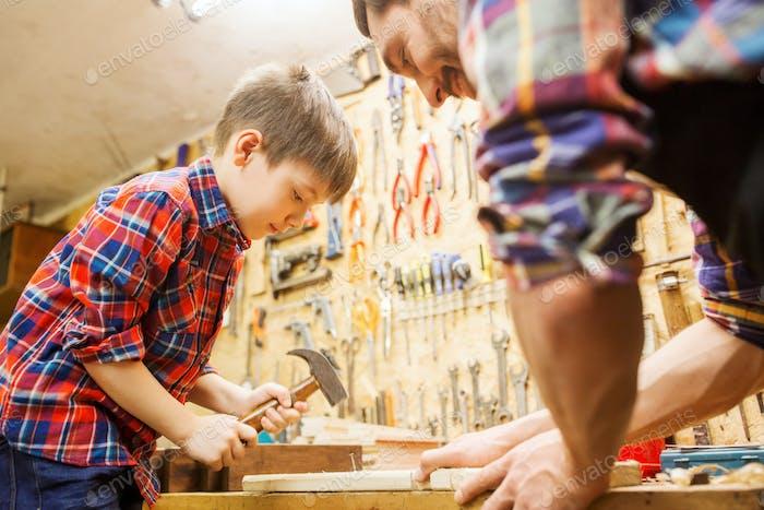 Vater und Sohn mit Hammer arbeiten in der Werkstatt