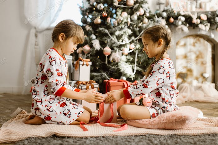 Two little sisters in pajamas sit on the carpet and open New Year's gifts in the light cozy room