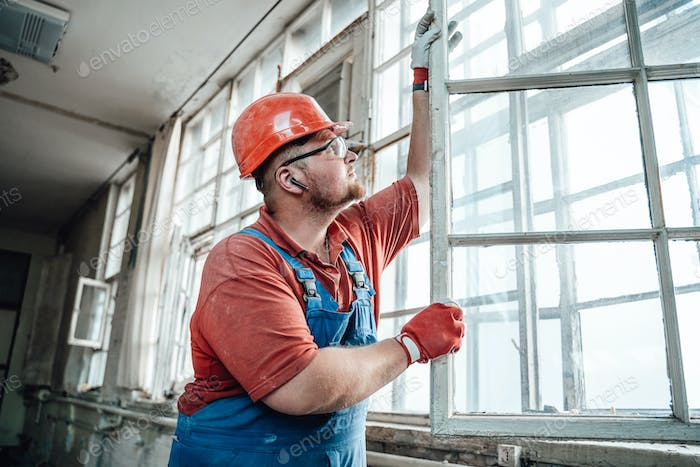 Concentrated builder working with a glass window at a construction site