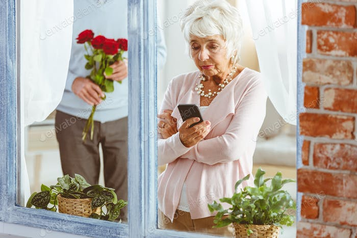 Man surprising woman looking at telephone