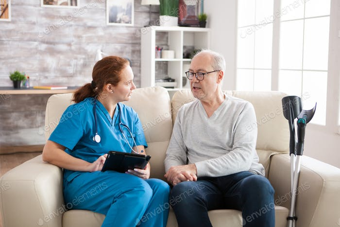 Young female caretaker sitting on couch with senior man
