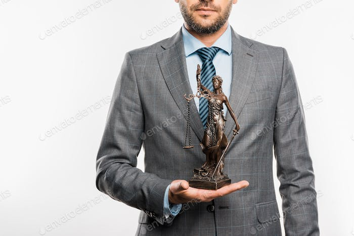 mid section of lawyer holding lady justice statue isolated on white