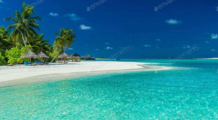 Palm trees and beach umbrelllas over lagoon and white sandy beac
