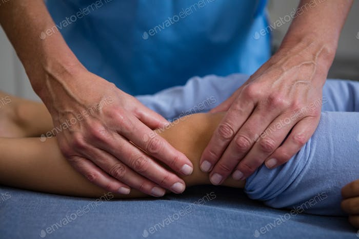 Physiotherapist giving leg massage to patient