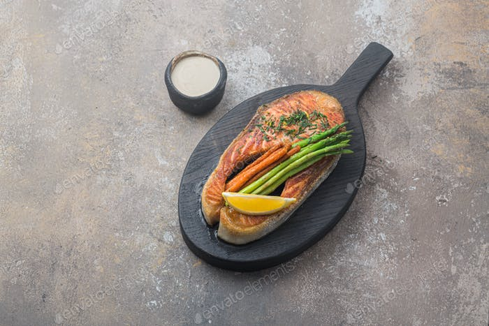 Grilled salmon steak with vegetables on wooden board, copy space