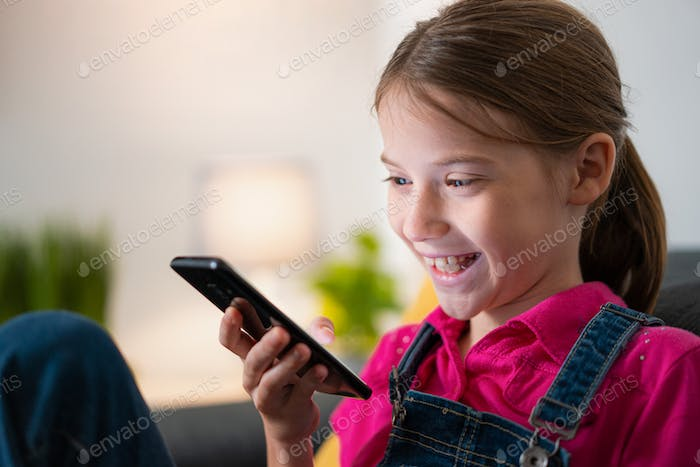 Young Little Girl Using Smartphone and Smiling Portrait With Copyspace
