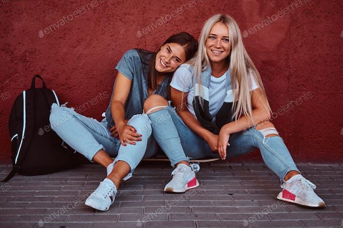 Porträt eines zwei lächelnden Hipster Mädchen sitzen zusammen auf Skateboard