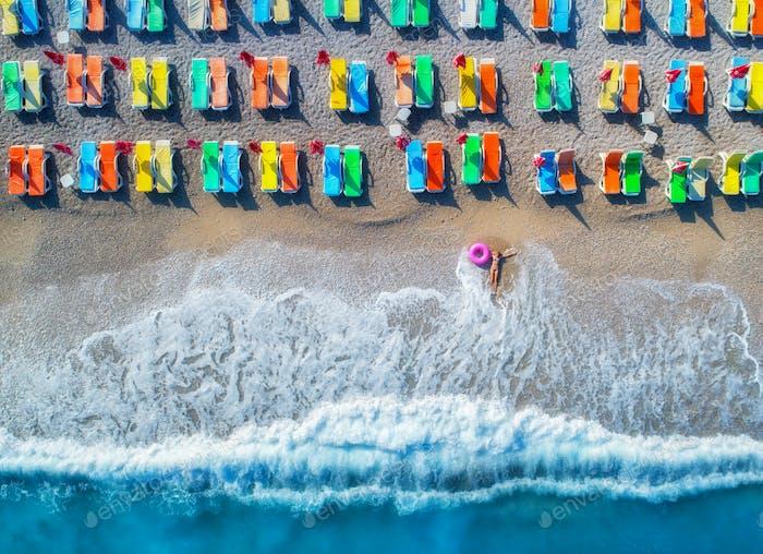 Luftaufnahme der liegenden Frau mit Schwimmring im Meer