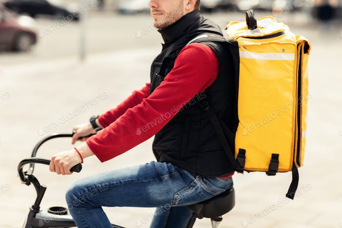 Unrecognizable Delivery Guy With Yellow Bag Riding Bike In City