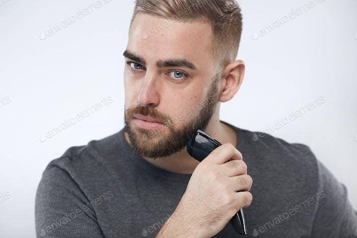 Young Man Trimming Beard