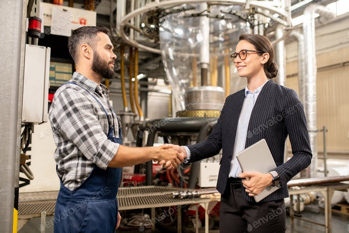 Two young business partners shaking hands after making deal in factory