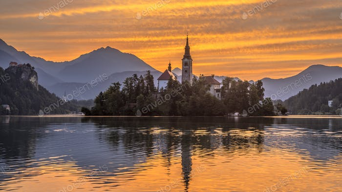 Lake bled with church under orange morning sky