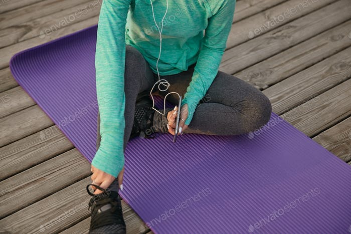 Photo of cute girl in bright sportswear, listening cool playlist on headphones after morning yoga