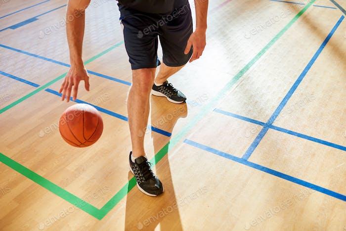 Crop man dribbling basketball ball