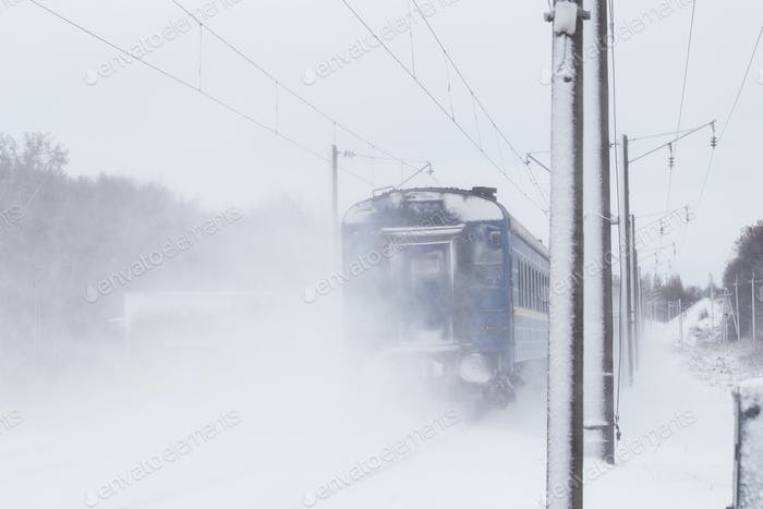 Passenger train rapidly moving along the snow track
