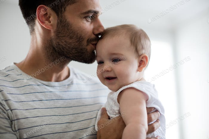 Father holding kissing his baby girl on forehead