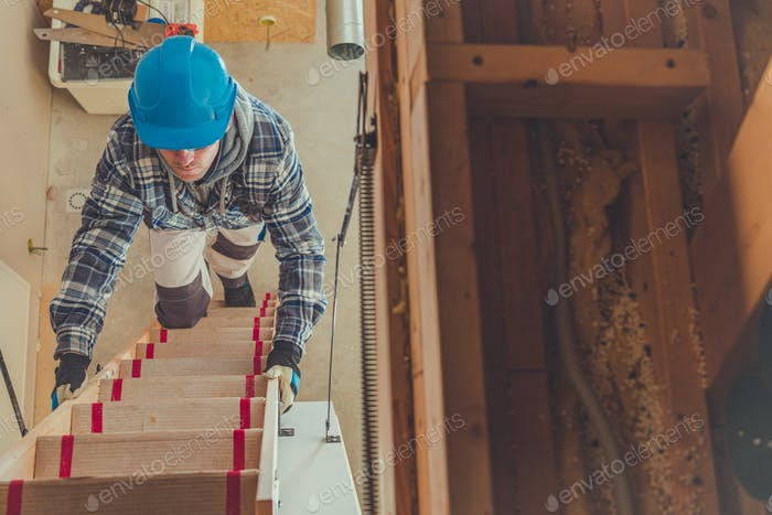 male Constrcution Worker Climbing Steps To Get To Second Floor Of House.