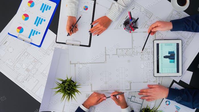 Инженеры, создающие схему элементов в зале заседаний